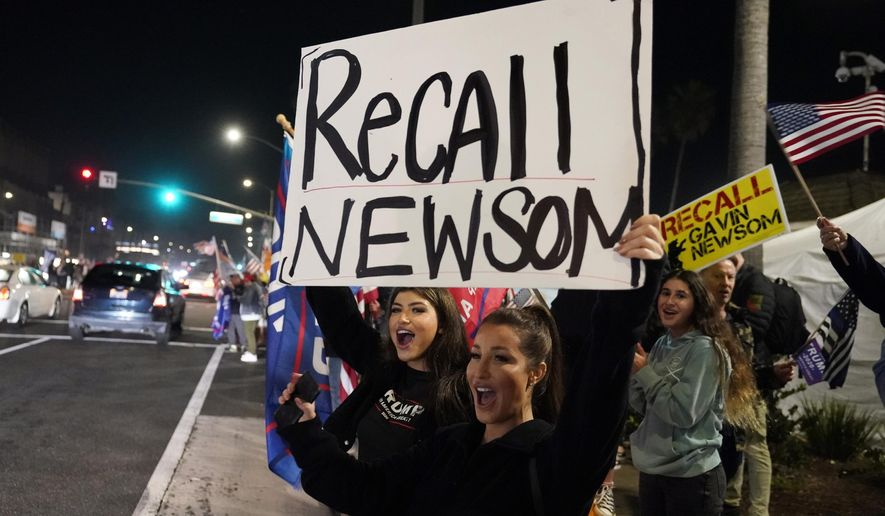 In this Nov. 21, 2020, file photo, Trump supporters shout slogans while carrying a sign calling for a recall on California Gov. Gavin Newsom during a protest against a stay-at-home order amid the COVID-19 pandemic in Huntington Beach, Calif. (AP Photo/Marcio Jose Sanchez, File)