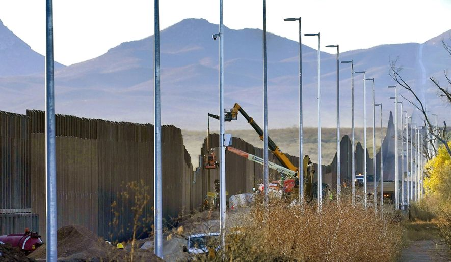 In this Dec. 8, 2020, file photo, crews construct a section of border wall in San Bernardino National Wildlife Refuge in Douglas, Ariz. (AP Photo/Matt York, File)