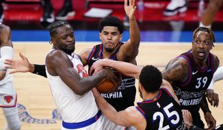 New York Knicks' Julius Randle, from left, battles for the ball against Philadelphia 76ers' Danny Green, Ben Simmons and Dwight Howard during the first half of an NBA basketball game, Tuesday, March 16, 2021, in Philadelphia. (AP Photo/Matt Slocum)