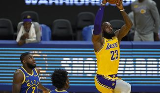 Los Angeles Lakers forward LeBron James (23) dunks in front of Golden State Warriors forward Eric Paschall (7) and center James Wiseman during the first half of an NBA basketball game in San Francisco, Monday, March 15, 2021. (AP Photo/Jeff Chiu)