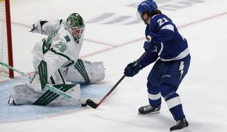 Tampa Bay Lightning center Brayden Point (21) gets the puck past Dallas Stars goaltender Jake Oettinger (29) to score a goal during the first period of an NHL hockey game in Dallas, Tuesday, March 16, 2021. (AP Photo/Michael Ainsworth)