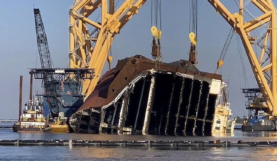 In this Feb. 25, 2021 photo, a towering crane straddles the capsized cargo ship Golden Ray, its interior decks exposed after the ship's bow was cut off and hauled away, off the coast of St. Simons Island, Ga. Salvage crews began Nov. 6 cutting the ship into giant chunks for removal. The vessel has been beached on its side since it overturned Sept. 8, 2019, soon after leaving port. (St. Simons Sound Incident response photo by Farrell Lafont of Gallagher Marine Systems via AP)
