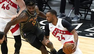 Toronto Raptors guard Norman Powell, right, drives against Chicago Bulls forward Patrick Williams during the first half of an NBA basketball game in Chicago, Sunday, March 14, 2021. (AP Photo/Nam Y. Huh)