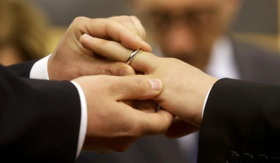 """FILE - In this May 21, 2015 file photo, Mauro Cioffari, left, puts a wedding ring on his partner Davide Conti's finger as their civil union is being registered by a municipality officer during a ceremony in Rome's Campidoglio Capitol Hill. The Vatican has decreed, Monday, March 15, 2021, that the Catholic Church cannot bless same-sex unions since God """"cannot bless sin."""" The Vatican's orthodoxy office, the Congregation for the Doctrine of the Faith, issued a formal response to a question about whether Catholic clergy can bless gay unions. (AP Photo/Gregorio Borgia, file)"""