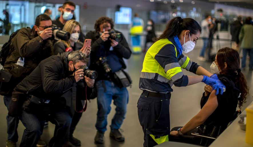 FILE - In this Thursday, Feb. 25, 2021 file photo a police officer receives an AstraZeneca vaccine during a mass COVID-19 vaccination campaign at Wanda Metropolitano stadium in Madrid, Spain. The Madrid regional government has started vaccinating its emergency services personnel. At least a dozen countries including Germany, France, Italy and Spain have now temporarily suspended their use of AstraZeneca's coronavirus vaccine after reports last week that some people in Denmark and Norway who got a dose developed blood clots, even though there's no evidence that the shot was responsible. The European Medicines Agency and the World Health Organization say the data available don't suggest the vaccine caused the clots and that people should continue to be immunized. Here's a look at what we know — and what we don't. (AP Photo/Manu Fernandez, File)