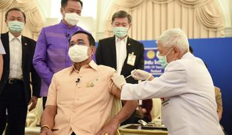 In this photo released by Government Spokesman Office, Thailand's Prime Minister Prayuth Chan-ocha, front left, receives a shot of the AstraZeneca's COVID-19 vaccine at government house in Bangkok, Thailand, Tuesday, March 16, 2021. (Government Spokesman Office via AP)