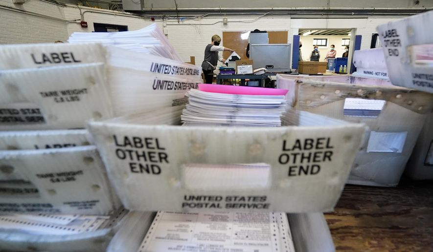 In this Nov. 4, 2020, file photo, Chester County election workers scan mail-in and absentee ballots for the 2020 general election in the United States at West Chester University, in West Chester, Pa. (AP Photo/Matt Slocum) ** FILE **