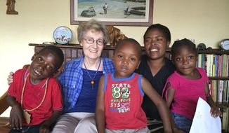 This 2018 photo provided by the Maryknoll Sisters shows Sister Janice McLaughlin with children in Zimbabwe. McLaughlin, a nun who was jailed and later deported by white minority-ruled Rhodesia, later Zimbabwe, for exposing human rights abuses, died on March 7, 2021, in Maryknoll, N.Y. She was 79. (Maryknoll Sisters via AP)