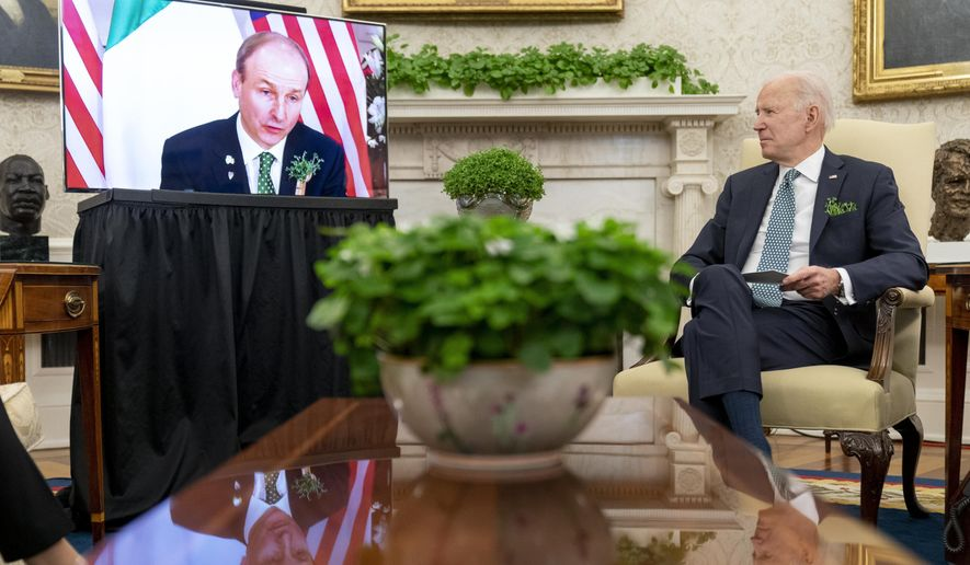 President Joe Biden watches as Ireland's Prime Minister Micheal Martin speaks via teleconference during a virtual meeting on St. Patrick's Day, in the Oval Office of the White House, Wednesday, March 17, 2021, in Washington. (AP Photo/Andrew Harnik)