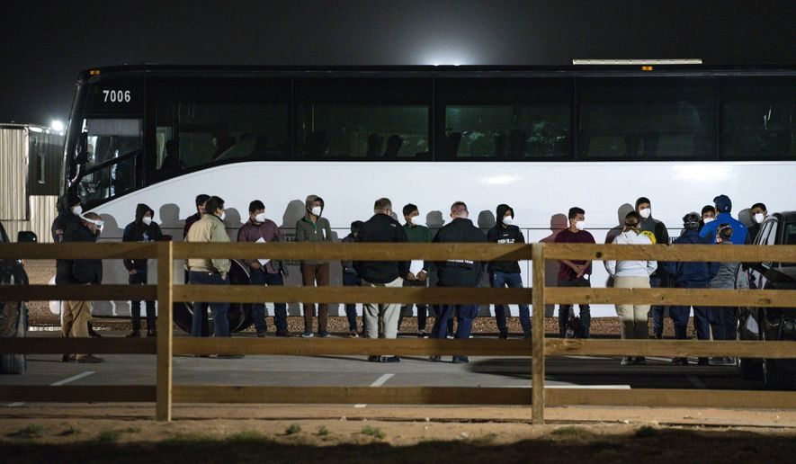 In this March 14, 2021, file photo, migrant children and teenagers are processed after entering the site of a temporary holding facility south of Midland, Texas. Migration flows to the U.S. from Mexico are surging for the third time in seven years under Republican and Democratic presidents — and for similar reasons. (Eli Hartman/Odessa American via AP, File)