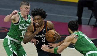 Cleveland Cavaliers' Collin Sexton (2) drives to the basket between Boston Celtics' Payton Pritchard (11) and Jayson Tatum (0) in the second half of an NBA basketball game, Wednesday, March 17, 2021, in Cleveland. The Cavaliers won 117-110. (AP Photo/Tony Dejak)