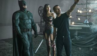 """This image released by HBO Max shows, from left, Ben Affleck as Batman, Gal Gadot as Wonder Woman and director Zack Snyder on the set of """"Zack Snyder's Justice League."""" (Clay Enos/HBO Max via AP)"""