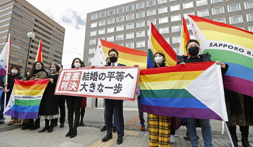 "Plaintiffs' lawyers and supporters hold rainbow flags and a banner that reads: ""Unconstitutional judgment"" outside Sapporo District Court after a court rule, in Sapporo, northern Japan, Wednesday, March 17, 2021. The court ruled the government's ban on same-sex marriages is unconstitutional, recognizing the rights of same-sex couples for the first time in the only Group of Seven country that doesn't acknowledge their legal partnership. (Yohei Fukai/Kyodo News via AP)"