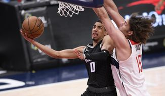 Sacramento Kings guard Tyrese Haliburton (0) goes to the basket against Washington Wizards center Robin Lopez (15) during the second half of an NBA basketball game, Wednesday, March 17, 2021, in Washington. (AP Photo/Nick Wass)