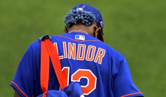 New York Mets infielder Francisco Lindor heads out for spring training baseball practice with his hair matching his uniform color Tuesday, Feb. 23, 2021, in Port St. Lucie, Fla. (AP Photo/Jeff Roberson)