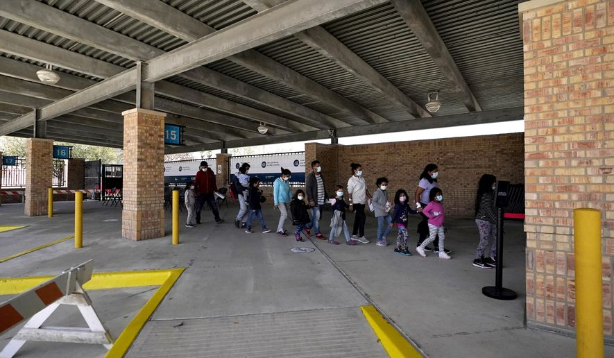 Migrants stand in line after being released from U.S. Customs and Border Protection custody at a bus station, Wednesday, March 17, 2021, in Brownsville, Texas. Team Brownsville, a humanitarian group, is helping the migrants reach their final destination in the U.S. A surge of migrants on the Southwest border has the Biden administration on the defensive. An official says U.S. authorities encountered nearly double the number children traveling alone across the Mexican border in one day this week than on an average day last month. (AP Photo/Julio Cortez)