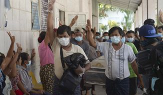 Relatives and friends of Khat Aung Phyo, a boy who was killed by bullet on March 14, raise a three-finger salute, a symbol of resistance, as his body is moved out from a mortuary in Yangon, Myanmar, Monday, March 15, 2021. Myanmar's ruling junta has declared martial law in six townships in the country's largest city, as security forces killed dozens of protesters over the weekend in an increasingly lethal crackdown on resistance to last month's military coup. (AP Photo)