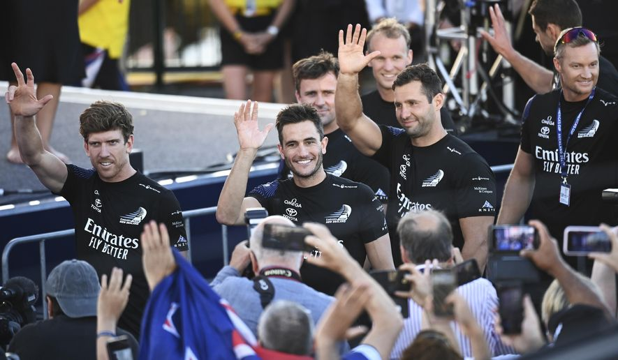 Emirates Team New Zealand helmsman Peter Burling, left, and teammates wave to supporters as they celebrate after defeating Italy's Luna Rossa in race 10 of the America's Cup on Auckland's Waitemata Harbour, Wednesday, March 17, 2021. Team New Zealand has retained the America's Cup by beating Italian challenger Luna Rossa 7-3 in the 36th match for sailing's oldest trophy. (Andrew Cornaga/Photosport via AP)