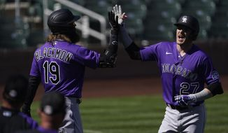 Colorado Rockies' Trevor Story (27) gets a high-five from Charlie Blackmon after Story hit a home run during the third inning of a spring training baseball game against the Arizona Diamondbacks Tuesday, March 9, 2021, in Scottsdale, Ariz. (AP Photo/Ashley Landis)