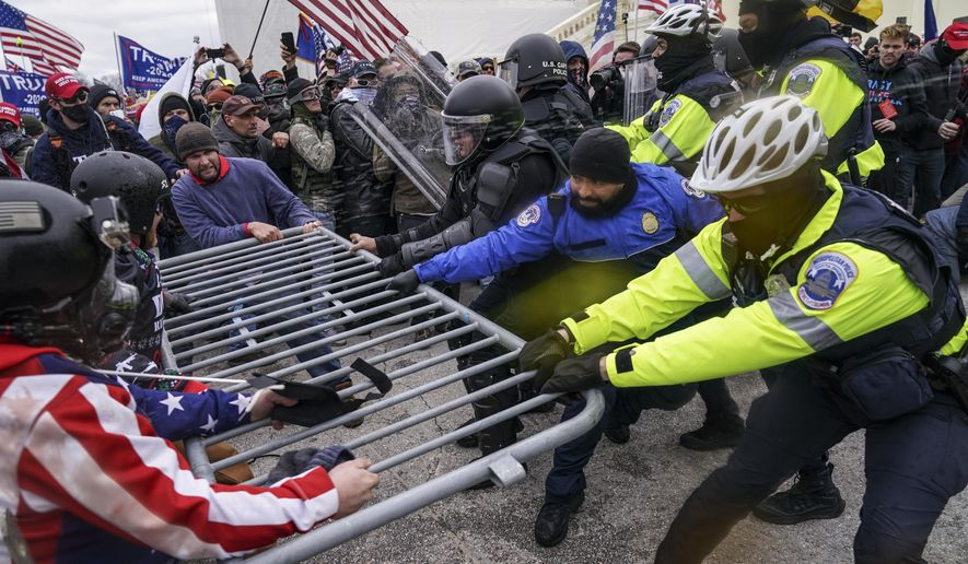 In this Jan. 6, 2021, file photo, violent Trump supporters try to break through a police barrier at the U.S. Capitol in Washington. (AP Photo/John Minchillo File)