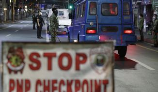 Police inspect vehicles at a checkpoint as curfew is imposed to prevent the spread of the coronavirus in metro Manila, Philippines a year after the country imposed a lockdown on Monday, March 15, 2021. The Department of Health has been reporting a surge in infections for more than a week, adding to concerns over a sluggish start of a vaccination campaign that has faced supply problems and public reluctance. (AP Photo/Aaron Favila)
