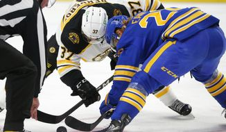 Buffalo Sabres forward Cody Eakin (20) and Boston Bruins forward Patrice Bergeron (37) take a faceoff during the first period of an NHL hockey game, Thursday, March 18, 2021, in Buffalo, N.Y. (AP Photo/Jeffrey T. Barnes)