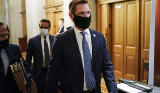 In this Feb. 10, 2021, file photo, Rep. Eric Swalwell, D-Calif., walks at the Capitol, in Washington. The House has rejected an attempt to boot a Democrat from the House intelligence committee. Democrats scuttled a Republican effort to remove Swalwell from the intelligence panel. The resolution against Swalwell cited reporting that he had contact more than six years ago with a suspected Chinese spy who targeted politicians in California. (Joshua Roberts/Pool via AP, File)