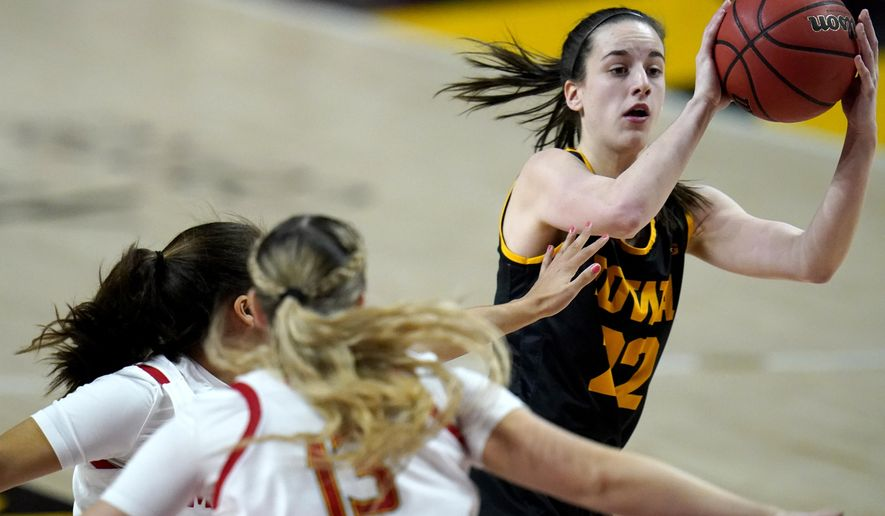Iowa guard Caitlin Clark, right, looks to pass to a teammate as she is pressured by Maryland guard Katie Benzan, left, and guard Faith Masonius during the first half of an NCAA college basketball game, Tuesday, Feb. 23, 2021, in College Park, Md. (AP Photo/Julio Cortez)