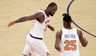 New York Knicks forward Reggie Bullock (25) is congratulated by forward Julius Randle after making a 3-point basket during the first half of the team's NBA basketball game against the Orlando Magic on Thursday, March 18, 2021, in New York. (AP Photo/Adam Hunger, Pool)