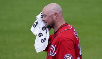 Washington Nationals starting pitcher Jon Lester wipes his face after warming up before a spring training baseball game against the New York Mets, Thursday, March 18, 2021, in Port St. Lucie, Fla. (AP Photo/Lynne Sladky)