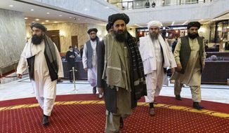 Taliban co-founder Mullah Abdul Ghani Baradar, center, arrives with other members of the Taliban delegation for an international peace conference in Moscow, Russia, Thursday, March 18, 2021. Russia is hosting a peace conference for Afghanistan, bringing together government representatives and their Taliban adversaries along with regional observers in a bid to help jump-start the country's stalled peace process. The one-day gathering Thursday is the first of three planned international conferences ahead of a May 1 deadline for the final withdrawal of U.S. and NATO troops from the country, a date fixed under a year-old agreement between the Trump administration and the Taliban. (AP Photo/Alexander Zemlianichenko, Pool) **FILE**