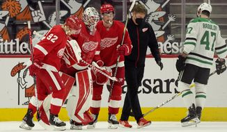 Detroit Red Wings goaltender Jonathan Bernier (45) is helped by center Vladislav Namestnikov (92) and center Dylan Larkin (71) skate off the ice during the second period of an NHL hockey game against the Dallas Stars, Thursday, March 18, 2021, in Detroit. (AP Photo/Carlos Osorio)