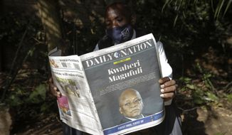 """A man reads a copy of the Daily Nation morning newspaper reporting the death of neighboring Tanzania's President John Magufuli on a street in Nairobi, Kenya Thursday, March 18, 2021. Magufuli, a prominent COVID-19 skeptic whose populist rule often cast his country in a harsh international spotlight, died Wednesday aged 61 of heart failure, it was announced by Vice President Samia Suluhu. Headline in Swahili reads """"Goodbye Magufuli."""" (AP Photo/Khalil Senosi)"""