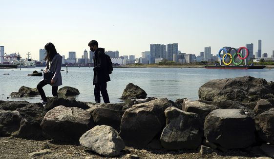 A couple wearing face masks walk on rocks with a backdrop of the Olympic rings floating in the water in Tokyo's Odaiba section Thursday, March 18, 2021. Japan on Thursday will approve ending a monthslong state of emergency in Tokyo set up to curb the spread of the coronavirus, despite concerns of a resurgence ahead of the spring party season and next week's Olympic torch relay. (AP Photo/Eugene Hoshiko)