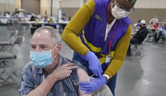 FILE - Garry Garff receives his Pfizer COVID-19 vaccination on March 10, 2021, in Sandy, Utah. Utah adults can begin signing up for a COVID-19 vaccine on March 24 — one week earlier that previously planned because the state has unallocated doses, Gov. Spencer Cox said Thursday, March 18, 2021. (AP Photo/Rick Bowmer, File)