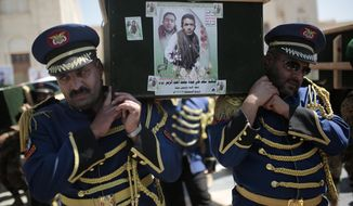 FILE - In this Feb. 16, 2021 file photo, honor guards carry coffins adorned with photographs of Houthi rebel fighters who who were killed in recent fighting with forces of Yemen's Saudi-backed internationally recognized government during their funeral procession, in Sanaa, Yemen. An offensive by Yemen's Iran-backed Houthi rebels in the province of Marib has already displaced hundreds of thousands, but it is also sparking fighting on the country's other front lines and endangering peace efforts to end the grinding civil war. (AP Photo/Hani Mohammed, File)