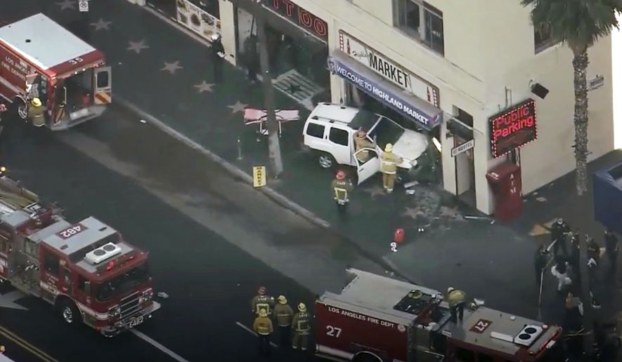 This aerial screenshot released by FOX 11 KTTV shows Los Angeles firemen at the scene of an accident on West Hollywood Boulevard in the Hollywood district of Los Angeles, Friday, March 19, 2021. The FOX 11 television station's crew members, reporter Hal Eisner and photojournalist Joab Perez, were working on a story about the famous El Capitan Theatre and Los Angeles County's partial reopening this week, which allows for movie theaters to open at limited capacity, according to FOX 11. The male driver has been arrested on suspicion of driving under the influence, the Los Angeles Police Department said. He told police he fell asleep at the wheel but failed field sobriety tests. (FOX 11 KTTV via AP)