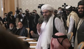 Former Afghan President Hamid Karzai, second left, looks as members of the Taliban delegation arrive for attending an international peace conference in Moscow, Russia, Thursday, March 18, 2021. (AP Photo/Alexander Zemlianichenko, Pool) ** FILE **