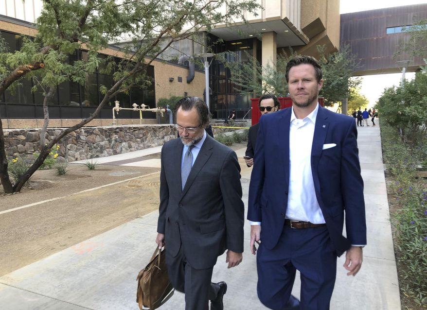 FILE - In this Nov. 5, 2019, file photo, then-Maricopa County Assessor Paul Petersen, right, and his attorney, Kurt Altman, leave a court hearing in Phoenix. Petersen, a former Phoenix politician already in prison on a six-year sentence for operating an illegal adoption scheme involving women from the Marshall Islands, was ordered Friday, March 19, 2021, to serve another five years behind bars for defrauding Arizona's Medicaid system in a scam to get taxpayer-funded health coverage for the birth mothers, even though he knew they didn't live in the state. (AP Photo/Jacques Billeaud, File)