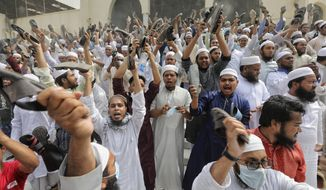 Bangladeshis raise their footwear and shout slogans during a protest after Friday prayers, against the visit of Indian Prime Minister Narendra Modi in Dhaka, Bangladesh, Friday, March 19, 2021. Hundreds of people including Muslim devotees and left-leaning student activists on Friday rallied in Bangladesh's capital to denounce the upcoming visit of Indian Prime Minister Narendra Modi to join the celebration of the country's 50th anniversary of independence. (AP Photo/Mahmud Hossain Opu)