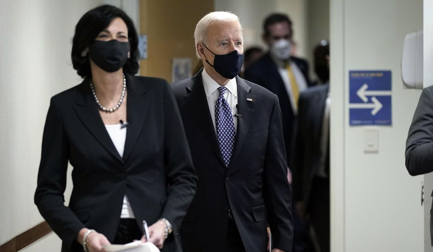 Dr. Rochelle Walensky, director of the Centers for Disease Control and Prevention, leads President Joe Biden into the room for a COVID-19 briefing at the headquarters for the CDC, Friday, March 19, 2021, in Atlanta. (AP Photo/Patrick Semansky)