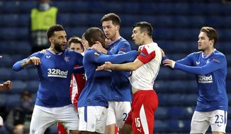 Rangers Glen Kamara, center, is held back by teammates as he reacts near the end of the Europa League Round of Sixteen soccer match between Rangers and Slavia Prague, at Ibrox Stadium, in Glasgow, Scotland,  Thursday March 18, 2021. (Andrew Milligan/PA via AP)