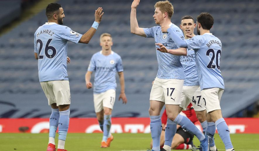 Manchester City's Kevin De Bruyne, centre, celebrates after scoring his side's opening goal during the English Premier League soccer match between Manchester City and Southampton at the Etihad Stadium in Manchester, England, Wednesday, March 10, 2021. (Martin Rickett/Pool via AP)