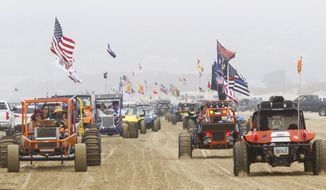 FILE - In this Sunday, Aug. 18, 2018, photo hundreds of dune buggies parade along the Oceano Dunes State Recreational Vehicle Area, the line stretching south to north in Oceano, Calif. The California Coastal Commission has voted to end off-highway vehicle use at Oceano Dunes State Vehicular Recreation Area within three years, a decision that follows years of debate over environmental and cultural impacts. The 10-0 vote Thursday, March 18, 2021, calls for the prohibition to take effect by 2024 at Oceano Dunes, the only California state park that allows recreational driving on the beach and in dunes. (David Middlecamp/The Tribune (of San Luis Obispo) via AP)