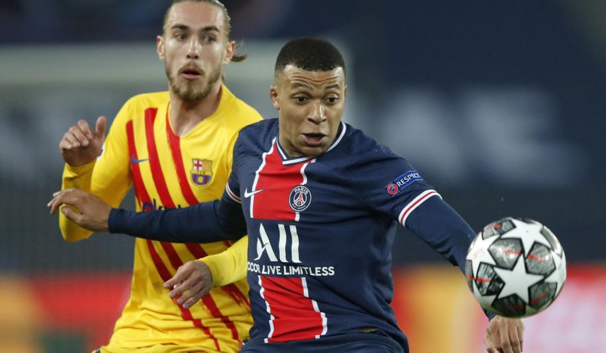 PSG's Kylian Mbappe, right, is challenged by Barcelona's Oscar Mingueza during the Champions League, round of 16, second leg soccer match between Paris Saint-Germain and FC Barcelona at the Parc des Princes stadium in Paris, Wednesday, March 10, 2021. (AP Photo/Christophe Ena)