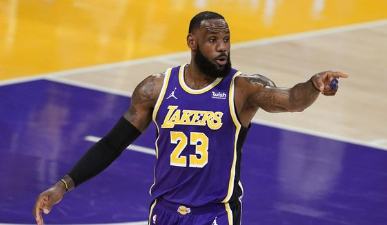 Los Angeles Lakers forward LeBron James signals to a teammate during the first half of an NBA basketball game against the Charlotte Hornets on Thursday, March 18, 2021, in Los Angeles. (AP Photo/Marcio Jose Sanchez) **FILE**