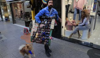 Ibrahim Farshoukh, 28, owner of a leather bracelets and bags shop, carries a stand with his products, on Beirut's commercial Hamra Street, in Beirut, Lebanon, Tuesday, March 16, 2021. More than half the population now lives in poverty, while an intractable political crisis heralds further collapse and Lebanese are gripped by fear for the future. (AP Photo/Hussein Malla)