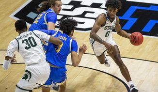 Michigan State's Aaron Henry (0) drives near teammate Marcus Bingham Jr. (30) as UCLA's Mac Etienne (12) and Johnny Juzang (3) defend during the first half of a First Four game in the NCAA men's college basketball tournament Thursday, March 18, 2021, at Mackey Arena in West Lafayette, Ind. (AP Photo/Robert Franklin)