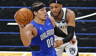 Orlando Magic forward Aaron Gordon (00) passes the ball as Brooklyn Nets forward Bruce Brown, right, guards him during the first half of an NBA basketball game, Friday, March 19, 2021, in Orlando, Fla. (AP Photo/John Raoux)