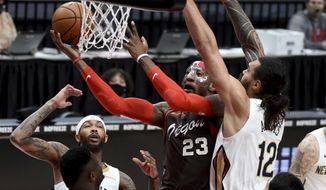 Portland Trail Blazers forward Robert Covington center, drives to the basket on New Orleans Pelicans center Steven Adams, right, and forward Brandon Ingram, left, during the first half of an NBA basketball game in Portland, Ore., Thursday, March 18, 2021. (AP Photo/Steve Dykes)